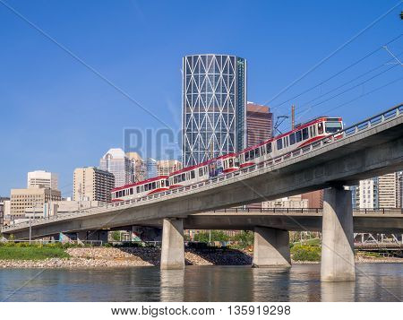 CALGARY, CANADA - JUNE 5: C-train crossing the Bow River on June 5, 2016 in Calgary, Alberta Canada. The C-Train is Calgary's main light rail transit system.