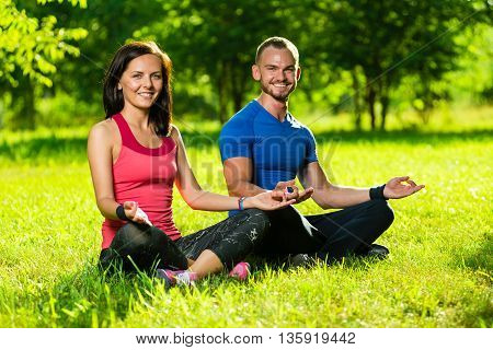Young man and woman doing yoga in the sunny summer park. Couples Yoga on green grass outdoor.