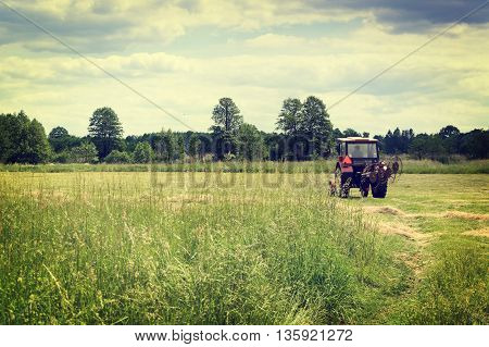 Old red tractor on green agriculture meadow - vintage effect