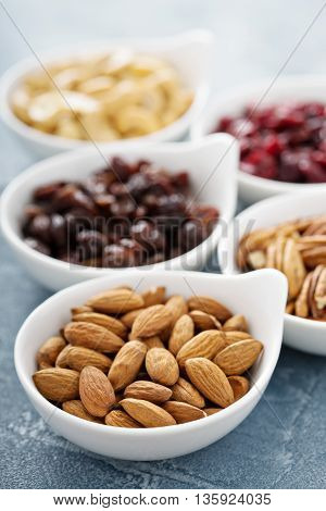 Variety of nuts and dried fruits in small white bowls healthy snacks