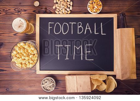 Football Fans Concept Of Beer Bottle In Brown Paper Bag,  Chips, Pistachio And Handwriting Text Foot