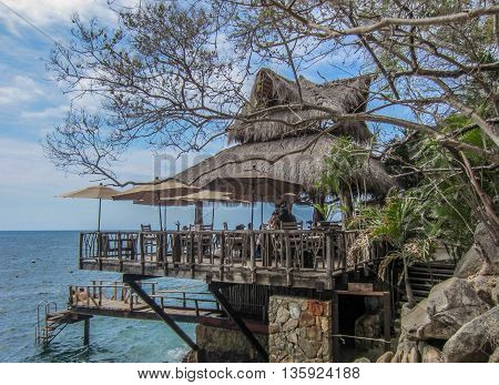 Thatched-roof cliff-side restaurant with umbrellas, tables and chairs hanging over blue ocean with sky of white puffy clouds.