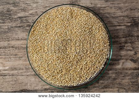 Quinoa in glass dish on wooden background view from above closeup.