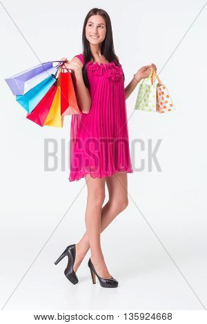 Happy shopping. Young woman in red dress holding multicolored shopping bags