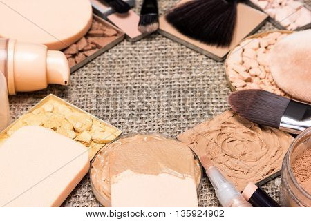 Makeup products and accessories to even out skin tone and create the perfect complexion on sackcloth. Shallow depth of field. Copy space