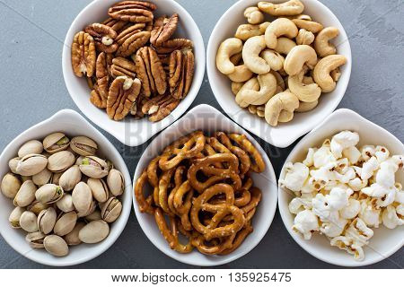 Variety of healthy snacks in white bowls pretzels and nuts
