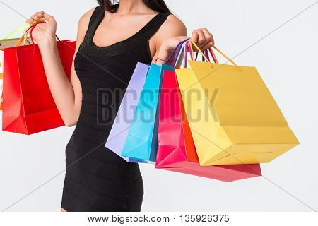 Happy shopping. Unrecognizable woman in black dress holding multicolored shopping bags