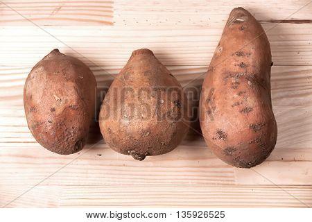 Sweet organic grown potatos natural light on wooden background