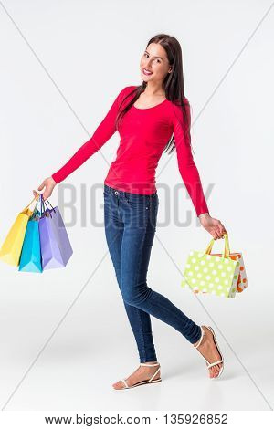Happy shopping. Young woman in red short and jeans holding multicolored shopping bags