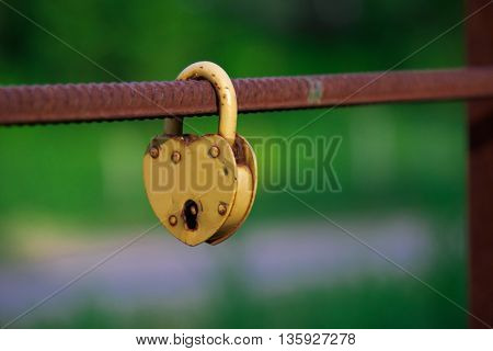 yellow padlock weighs on metal fittings green background