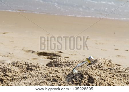Empty glass bottle on the beach with copy space Minimalist
