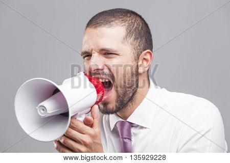Young business man shouting by megaphone on gray background