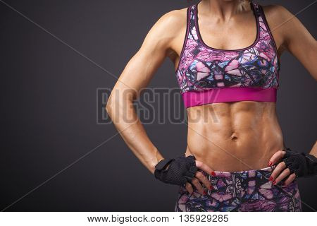 Cropped image of female model with muscular body on dark background