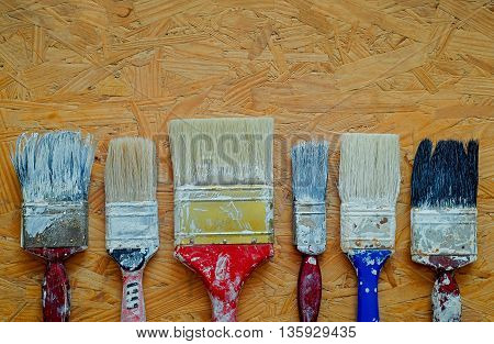 Old paint brushes on pressed wooden panel background