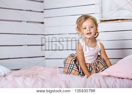 Beautiful little girl sitting on bed. Blue-eyed blonde.Children's room. Happy small girl portrait.