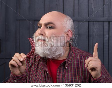 Old bearded man with long grey beard on smiling face in checkered shirt with red chilli pepper or capsicum on wooden wall background