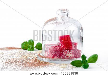 Turkish Delight sweets in glass vase on white background