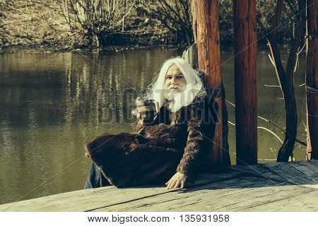 Old man on the porch with a drink in hands