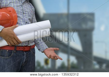 Engineer holding helmet and blueprint in hands over blurred construction background security