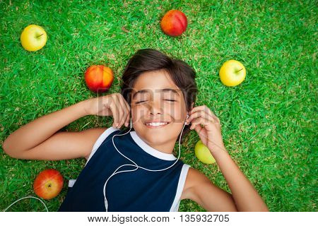 Portrait of a cute smiling teen boy listening to music, lying down on a fresh green grass field, happy summer holidays