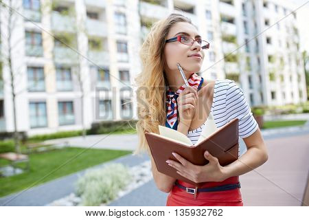 Young attractive happy student woman wearing  glasses holding a briefcase