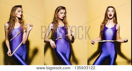 Attractive slim girl collage with long hair in violet second skin jumpsuit standing with tape-line around waist on yellow background