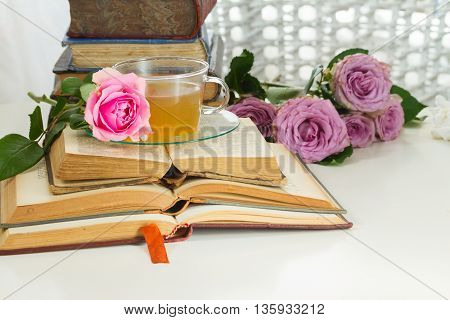 Pile of vintage books with bouqet of pink and violet rose flowers