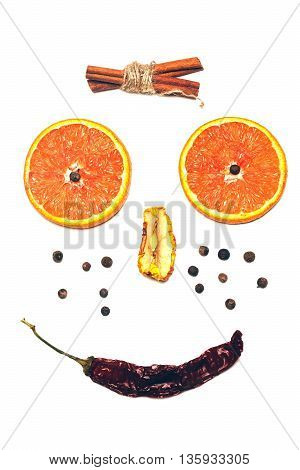 human smiling face smiley made of red chilli pepper dried apple allspice cinnamon sticks and orange slices isolated on white background