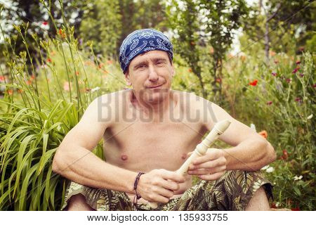 Smiling man with a flute in his hand sitting on the meadow and looking into the camera.