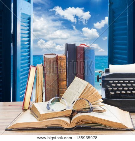 Old books, glasses and typewriter over open window to sea and sky background - writting and publishing concept