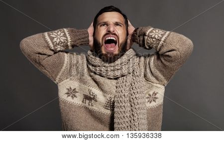 Close-up of young bearded man in pain yelling over grey background