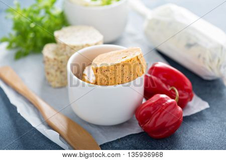 Variety of aromatic compound butters with herbs and chili