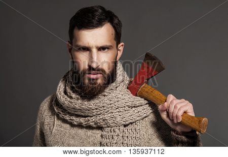 Evil young adult beaded man holding knife and ax looking at the camera. Fashion shot on grey background.