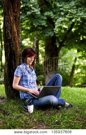 Beautiful young freelancer woman using laptop sitting under the tree in the park.Happy smiling girl working online.Studying and learning using notebook computer.Freelance workbusiness people concept.
