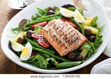 Grilled salmon nicoise salad with potatoes, olives, salad leaves