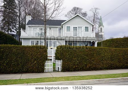 A home behind an arborvitae (Thuja occidentalis) hedge, next to Zorn Park in Harbor Springs, Michigan.