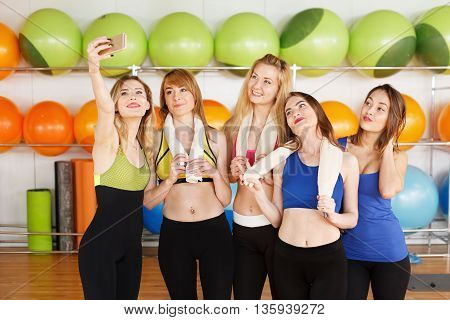 Making selfie. Group of girls in fitness class at the break looking at cell phone, happy, laugh. Girls do selfie after fitness training. Girl friendship, happiness, modern life, young people concept.