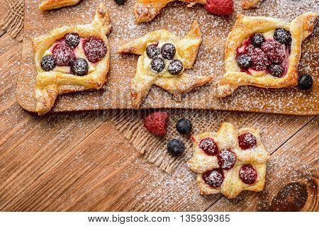 Puff pastries with raspberries, blueberries and cream cheese on wooden background.
