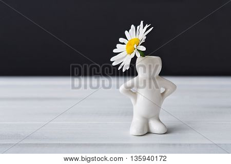 Beautiful daisy in small white ceramic vase in form of man on white table at black background. Small man with flower head. Flower with copy space. Funny vase, black and white. Flower present