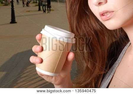 Depressed woman with takeaway coffee cup in hands part of the face shot instagram effect
