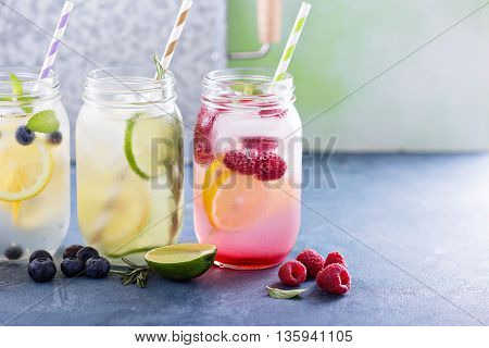 Variety of lemonade in mason jars with berries and fruits
