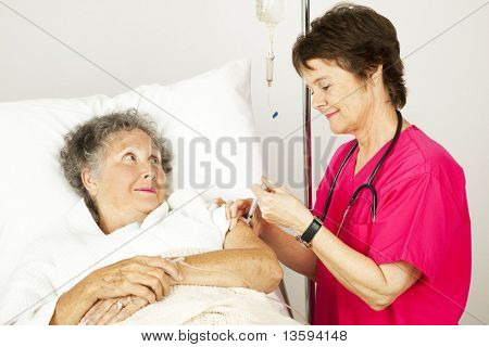 Hospital nurse giving an elderly female patient an injection in her arm.