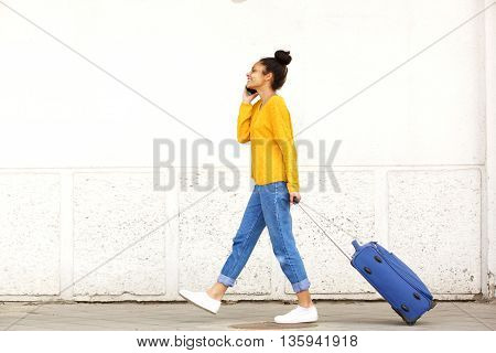 Young Woman Traveling With Suitcase And Mobile Phone