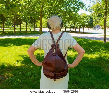 The back view of senior gray woman with earphones in the park