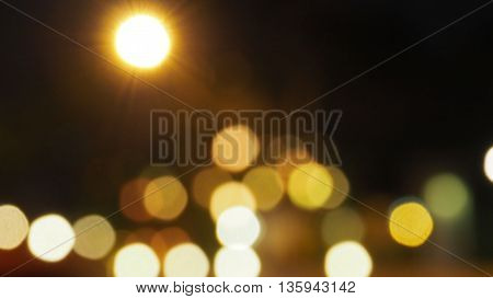 Street lamp lighting look like the sunrise at night time and car lighting bokeh blur on the road are circle shape.