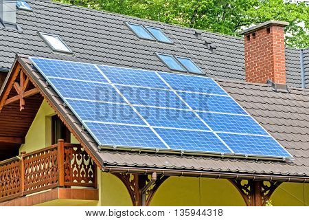 Modern solar cells on the roof of the brown family house.