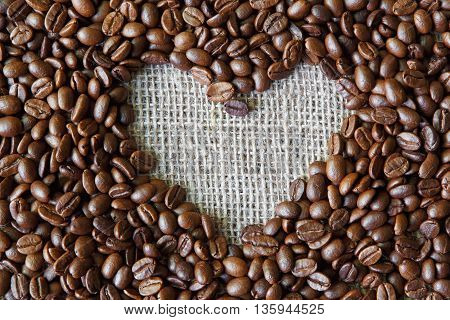 Plenty of coffee beans and burlap texture heart shape background, love symbol. Sack cloth canvas with copy space. Seeds at hessian textile