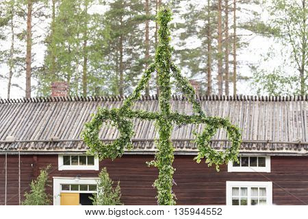 Swedish Traditional Midsummer Pole (Maypole) with a building in the background.