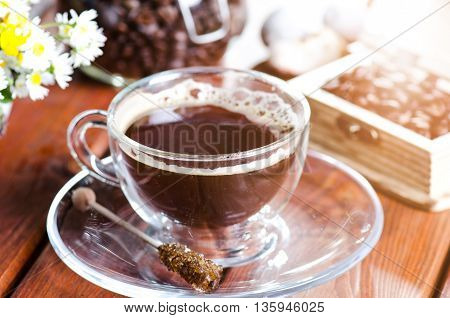cup of coffee on a wooden backgound. Flowers and grass. Natural background. Agricultural.Garden