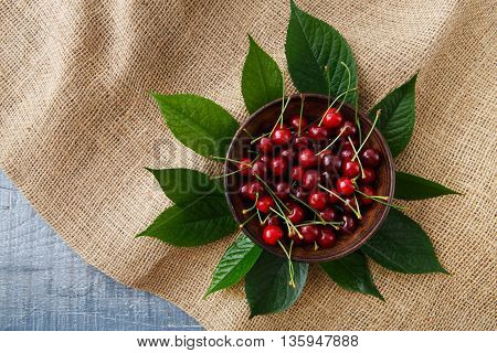 Sweet fresh cherries in a bowl with green leaves on blue rustic wood and sack cloth, fruit backround. Healthy food top view at hessian textile.
